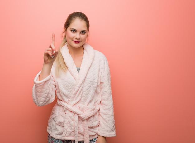 Jonge russische vrouw die pyjama draagt die nummer één toont