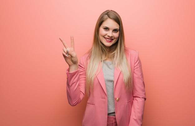 Jonge russische vrouw die pyjama draagt die nummer twee toont