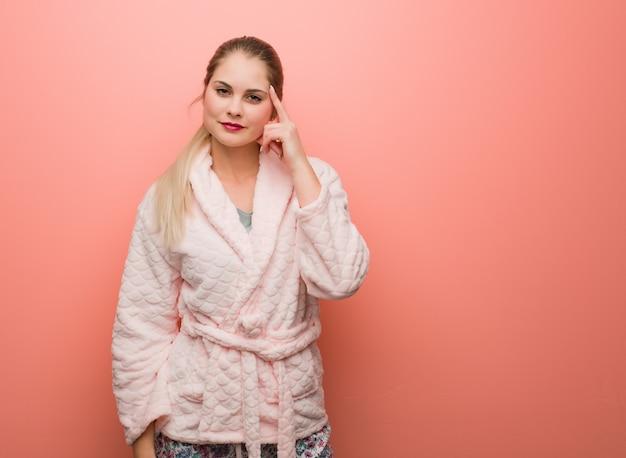 Jonge russische vrouw die pyjama draagt die over een idee denkt
