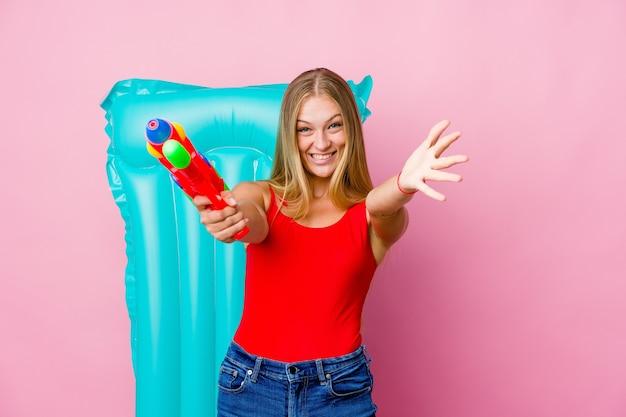 Jonge russische vrouw die speelt met een waterpistool met een luchtbed voelt zich zelfverzekerd door een knuffel te geven