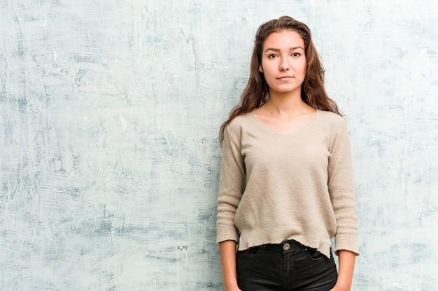 Jonge russische vrouw die tegen een grungemuur glimlacht