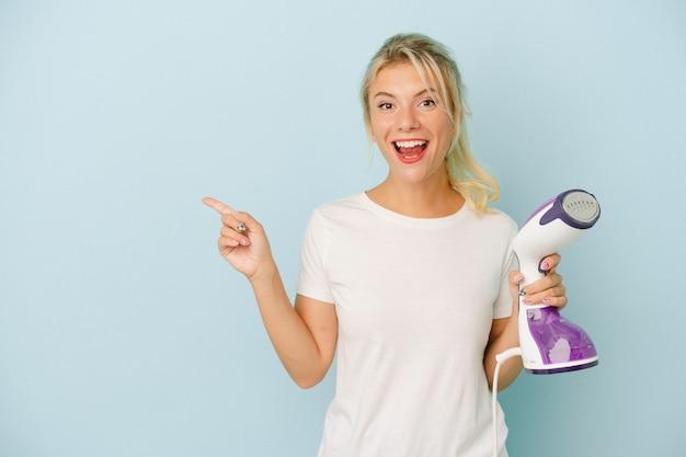 Jonge russische vrouw die verticaal ijzer houdt dat op blauwe achtergrond wordt geïsoleerd glimlacht en wijst opzij, iets tonend bij lege ruimte.