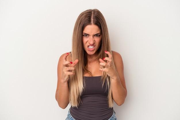Jonge russische vrouw geïsoleerd op een witte achtergrond boos schreeuwen met gespannen handen.