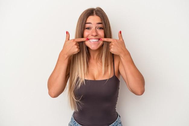Jonge russische vrouw geïsoleerd op een witte achtergrond glimlacht, wijzende vingers naar de mond.