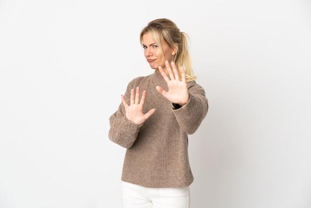 Jonge russische vrouw geïsoleerd op een witte achtergrond nerveus uitrekkende handen naar voren