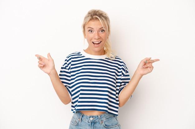 Jonge russische vrouw geïsoleerd op een witte achtergrond, wijzend naar verschillende kopieerruimten, een van hen kiezend, weergegeven met de vinger.