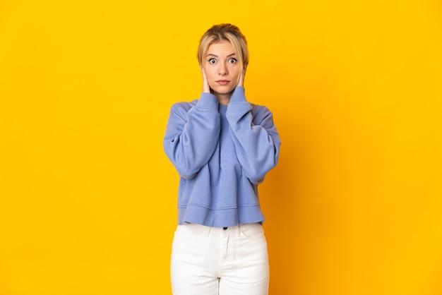 Jonge russische vrouw geïsoleerd op gele achtergrond gefrustreerd en die oren bedekt