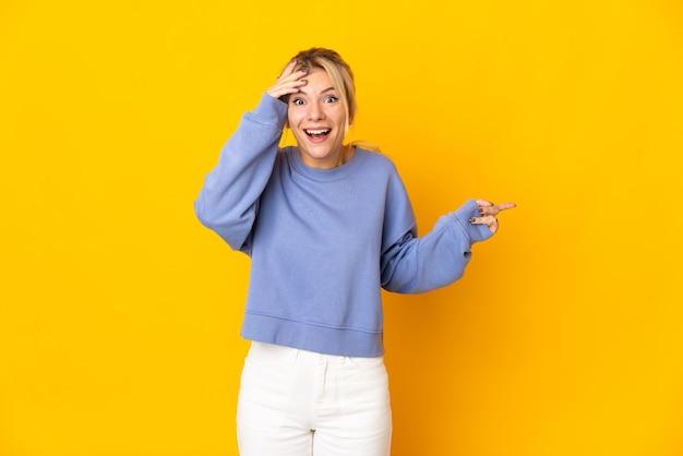 Jonge russische vrouw geïsoleerd op gele achtergrond verrast en wijzende vinger naar de zijkant Premium Foto