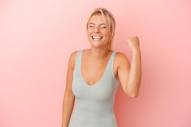 Jonge russische vrouw geïsoleerd op roze achtergrond die een overwinning, passie en enthousiasme, gelukkige uitdrukking viert.