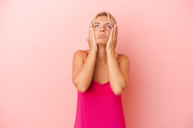 Jonge russische vrouw geïsoleerd op roze achtergrond jammerend en huilend troosteloos.