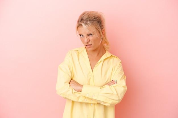 Jonge russische vrouw geïsoleerd op roze achtergrond ongelukkig in de camera kijken met sarcastische uitdrukking.