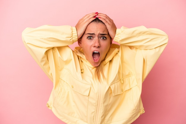 Jonge russische vrouw geïsoleerd op roze achtergrond verrast en geschokt.