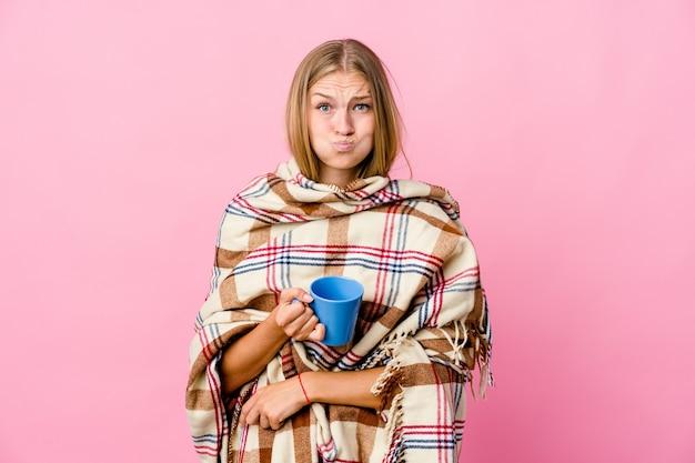 Jonge russische vrouw gewikkeld in een deken koffie drinken blaast wangen, heeft vermoeide uitdrukking. gezichtsuitdrukking concept.