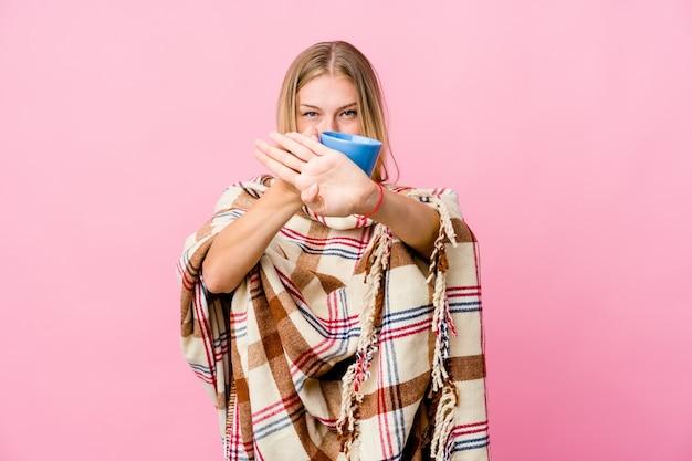 Jonge russische vrouw gewikkeld in een deken koffie drinken doet een ontkenningsgebaar