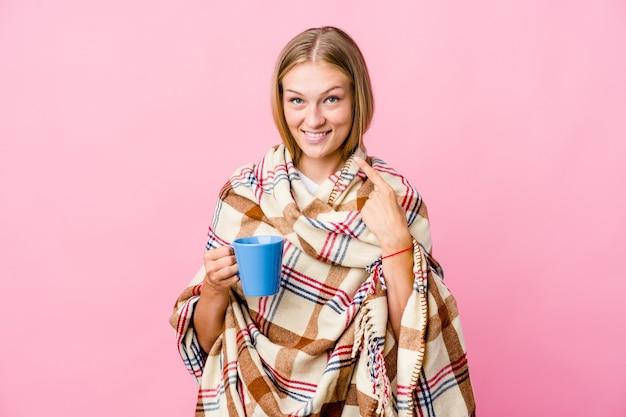 Jonge russische vrouw gewikkeld in een deken koffie drinken glimlacht, wijzende vingers naar mond