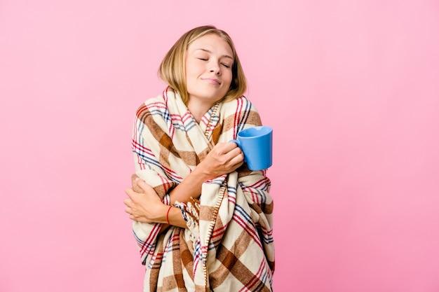 Jonge russische vrouw gewikkeld in een deken koffie drinken knuffels, zorgeloos en gelukkig glimlachen.