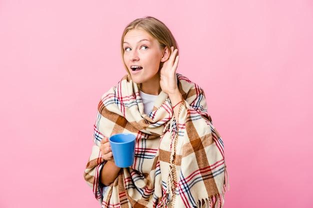 Jonge russische vrouw gewikkeld in een deken koffie drinken proberen te luisteren een roddels.