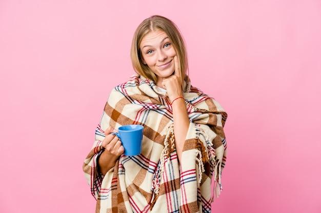 Jonge russische vrouw gewikkeld in een deken koffie drinken twijfelende tussen twee opties.