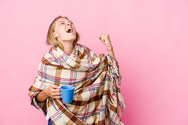 Jonge russische vrouw gewikkeld in een deken koffie drinken verhogen vuist na een overwinning, winnaar concept.
