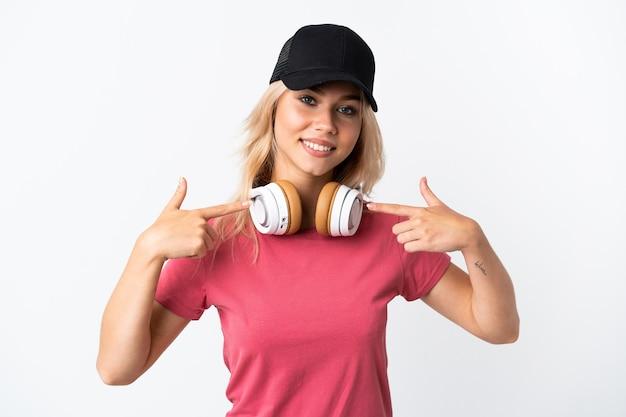 Jonge russische vrouw luisteren muziek geïsoleerd op een witte muur met een duim omhoog gebaar