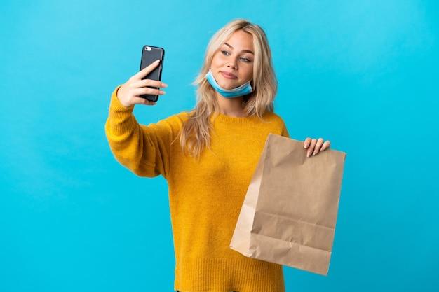 Jonge russische vrouw met een boodschappentas geïsoleerd op blauw een selfie maken
