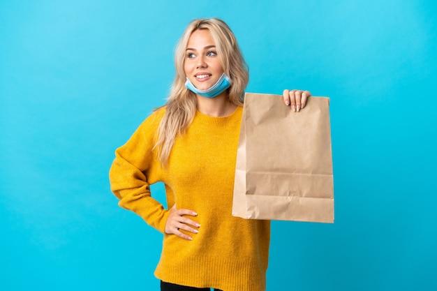 Jonge russische vrouw met een boodschappentas geïsoleerd op blauwe achtergrond poseren met armen op heup en glimlachen