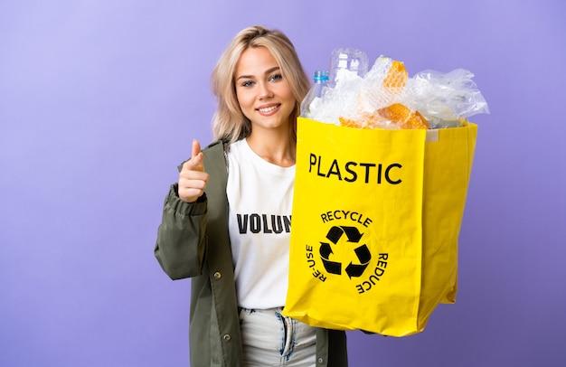 Jonge russische vrouw met een recyclingzak vol papier om te recyclen geïsoleerd op paarse muur wijzend naar voren en glimlachend