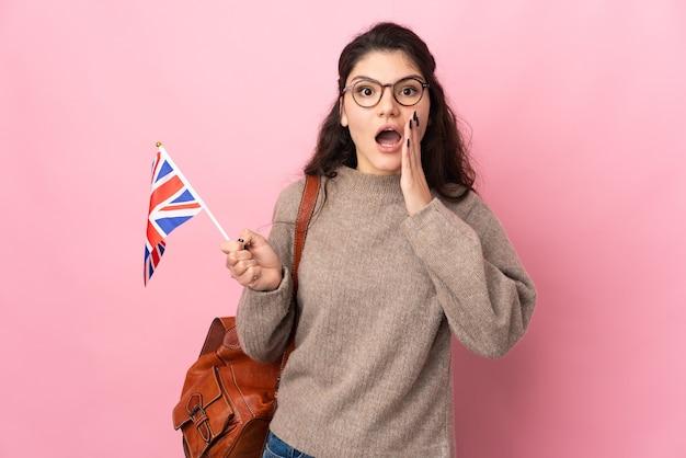 Jonge russische vrouw met een vlag van het verenigd koninkrijk geïsoleerd op roze muur met verbazing en geschokt gelaatsuitdrukking