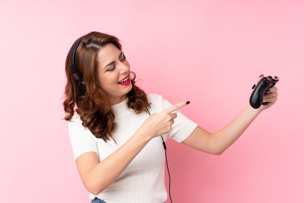 Jonge russische vrouw over geïsoleerde roze spelen als achtergrond bij videospelletjes