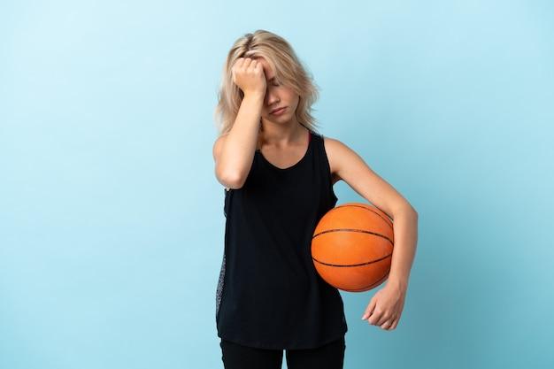 Jonge russische vrouw speelbasketbal geïsoleerd op blauw met hoofdpijn