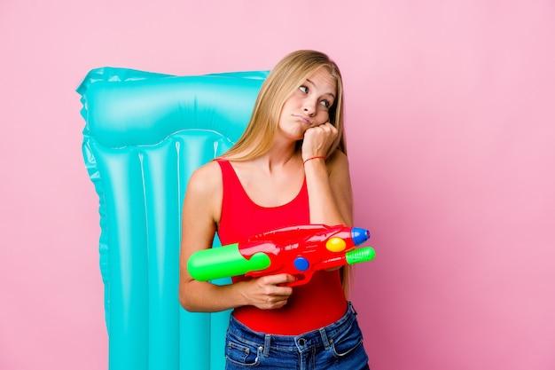 Jonge russische vrouw speelt met een waterpistool met een luchtbed die zich verdrietig en peinzend voelt, kijkend naar kopie ruimte.