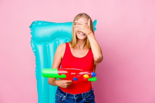 Jonge russische vrouw speelt met een waterpistool met een luchtbed heeft betrekking op de ogen met de handen, een brede glimlach wachtend op een verrassing.