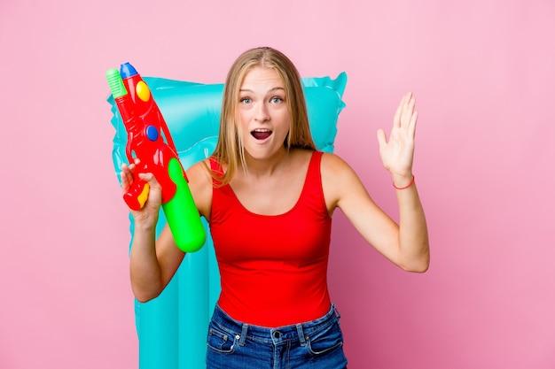 Jonge russische vrouw spelen met een waterpistool met een luchtbed een aangename verrassing ontvangen, opgewonden en handen opheffen.