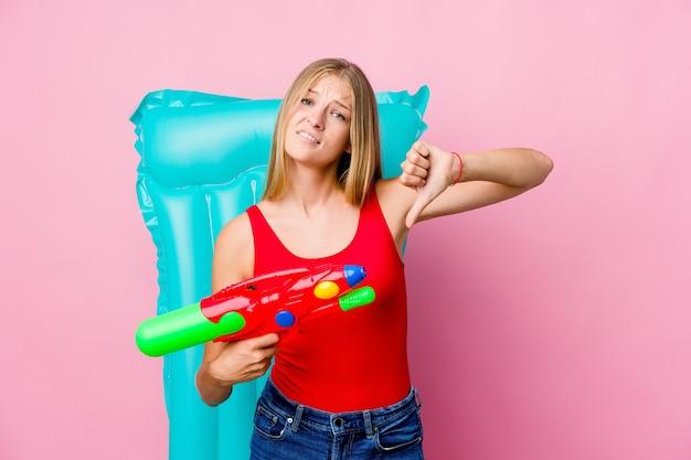 Jonge russische vrouw spelen met een waterpistool met een luchtbed met duim omlaag en afkeer uiten.