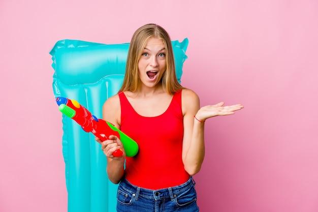 Jonge russische vrouw spelen met een waterpistool met een luchtbed verrast en geschokt.