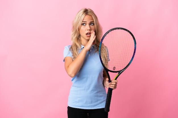 Jonge russische vrouw tennissen geïsoleerd op paars iets met verrassingsgebaar fluisteren terwijl ze naar de zijkant kijken