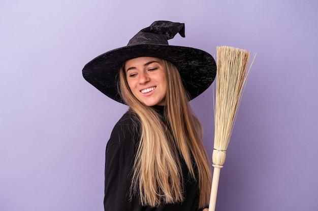 Jonge russische vrouw vermomd als een heks met een bezem geïsoleerd op een paarse achtergrond kijkt glimlachend, vrolijk en aangenaam opzij.