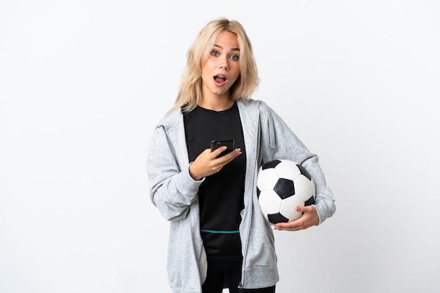 Jonge russische vrouw voetballen geïsoleerd op wit verrast en een bericht verzenden
