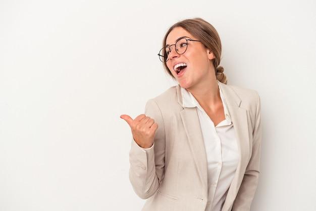 Jonge russische zakenvrouw geïsoleerd op een witte achtergrond wijst met duimvinger weg, lachend en zorgeloos.