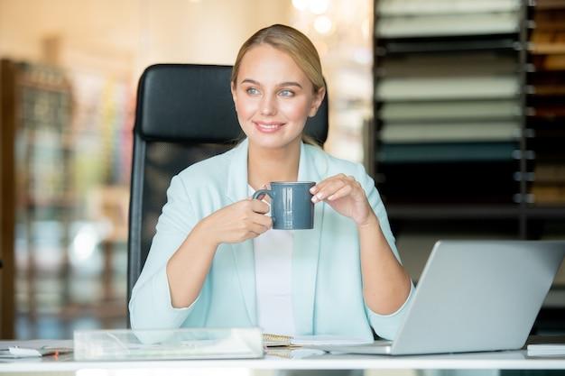Jonge rustgevende onderneemster met drankzitting door werkplaats terwijl het hebben van rust voor laptop