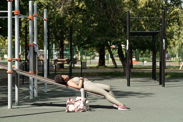 Jonge rustgevende sportvrouw ontspannen op sportfaciliteiten op sportveld