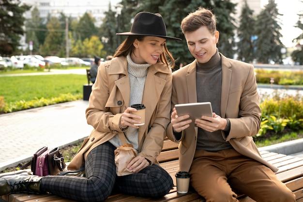 Jonge, rustgevende vrouw kijkt naar het scherm van de smartphone die door haar vriend wordt vastgehouden terwijl ze op de bank zit en chat en koffie drinkt