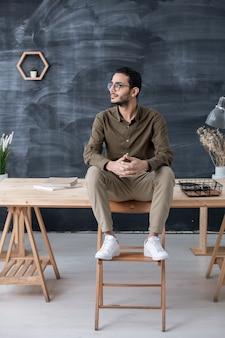 Jonge rustgevende zakenman in vrijetijdskleding, zittend op houten tafel met zijn voeten op stoel voor camera