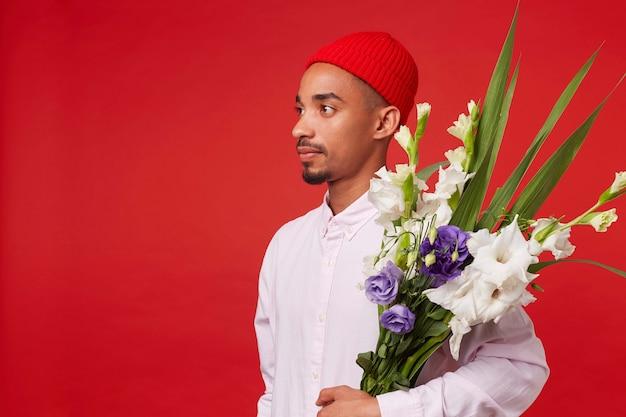 Jonge rustige afro-amerikaanse man in wit overhemd en rode hoed, kijkt weg en houdt boeket, staat op rode achtergrond.