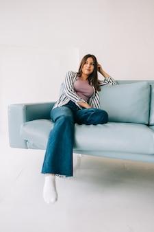 Jonge rustige blanke vrouw ontspannen, zittend op de bank in de moderne woonkamer