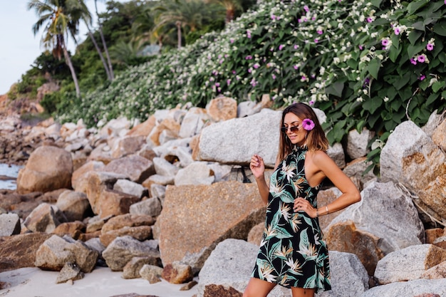Jonge rustige getatoeëerde vrouw in korte zomerjurk met tropische print op rotsachtig strand met groene struiken en paars roze bloemen