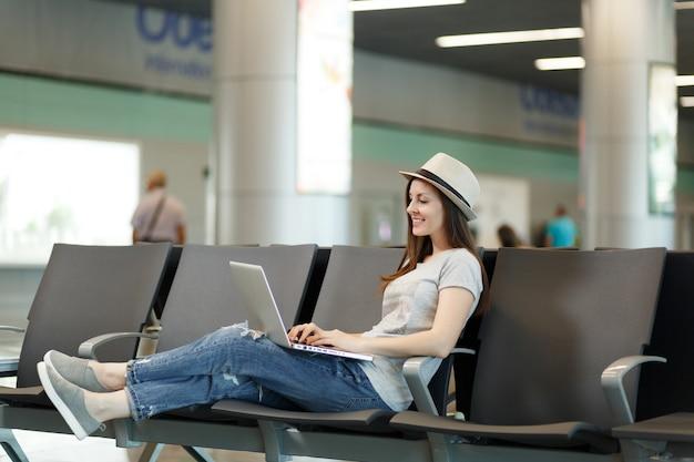 Jonge, rustige reizigerstoeristenvrouw met hoed die aan laptop werkt terwijl ze wacht in de lobby op de internationale luchthaven