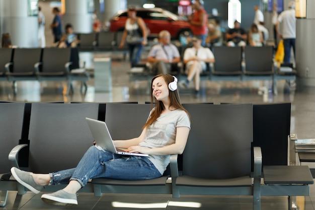 Jonge, rustige reizigerstoeristenvrouw met koptelefoon die muziek luistert die op laptop werkt, wacht in de lobby op de internationale luchthaven