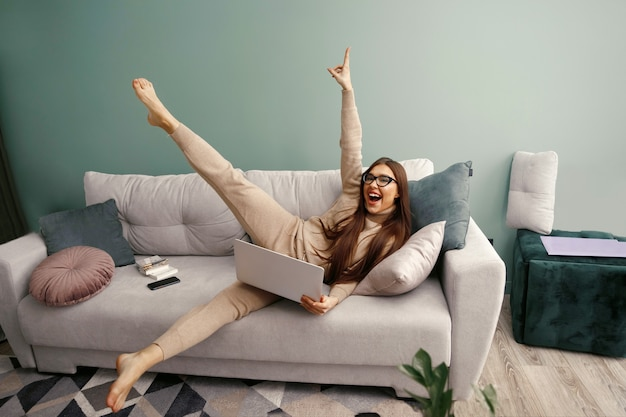 Jonge rustige vrouw met laptop ontspannen zitten op een comfortabele bank thuis na het werk, luie gelukkige vrouw meisje rustend op de bank geniet van gemoedsrust zonder stress op de bank. werkplek aan huis
