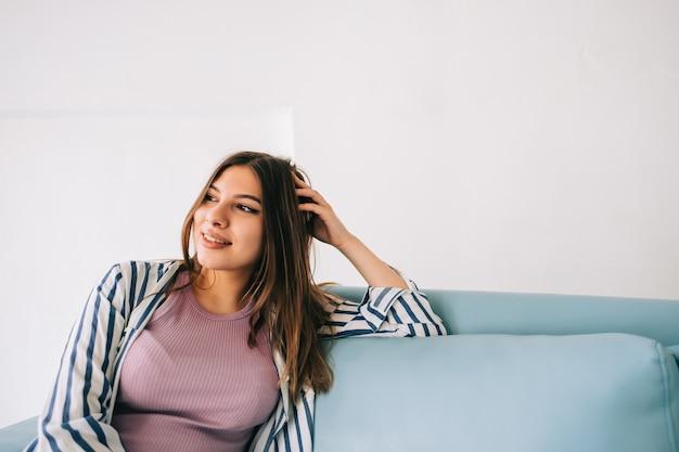 Jonge rustige vrouw ontspannen, zittend op de bank in de moderne woonkamer